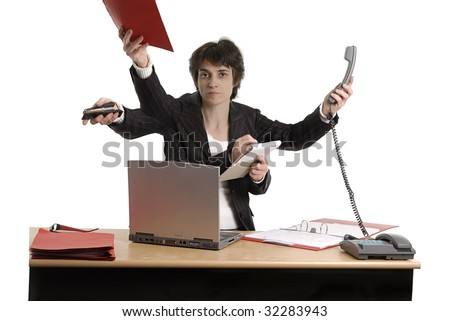 busines woman sitting at her desk doing multiple tasks - stock photo