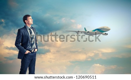 Businesman and plane on the background against cloudy sky - stock photo