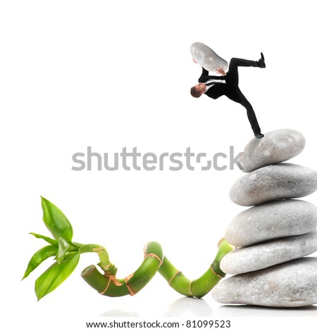 Business about to fall of a pebble pyramid - stock photo