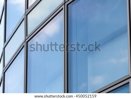 Business abstract - modern office building covered with glass.