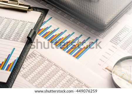Business accessories (notebook, magnifier, calculator, planchette, tablet, fountain pen, notebook, glasses) and graphics, tables, charts on a wooden office desk. Soft focus, lights effects.