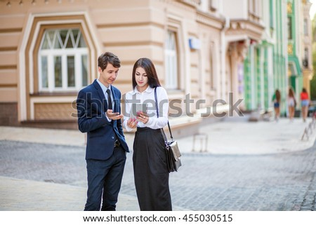 Business acquaintance of handsome businessman in blue suit and beautiful businesswoman in white blouse and black skirt. First meeting. Communication on city background. - stock photo