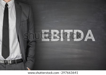 Business acronym EBITDA Earnings before interest and taxes depreciation and amortization on black blackboard with businessman - stock photo