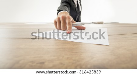 Business adviser showing to a piece of document with statistical data pushing it towards you on wooden office desk. - stock photo