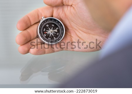 Business advisor holding compass. Over the shoulder view - stock photo