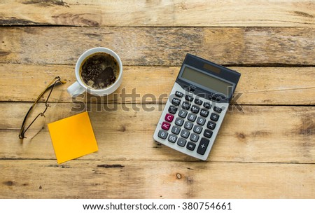 Business analysis concept. Top view , pen, calculator, glasses and coffee mug. Wooden table background. - stock photo