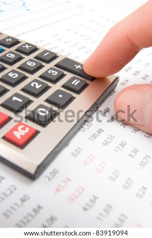 Business analyst calculate revenue - finger push button plus on calculator - stock photo