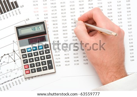 Business analyst - hand with pen; calculator, sheet and graph from top view - stock photo