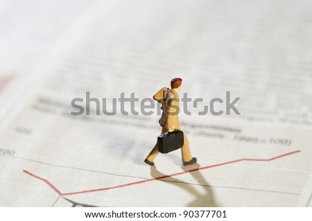 Business Analyst Troubleshooting Flatline Graph, concept with miniature model of businessman walking along a flatline graph with his briefcase. - stock photo