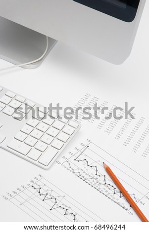 Business analyst workplace - pencil, sheet with numbers, graph, keyboard and part of computer - stock photo