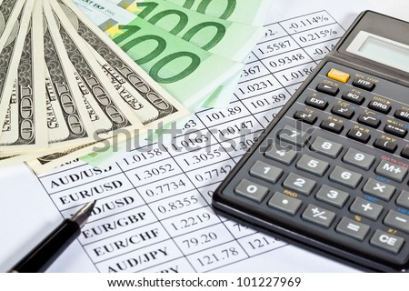 Business analytics: closeup of paper money, calculator and pen on currency cross-rate table