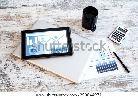 Business Analytics on a wooden Desk with a Tablet PC and a Laptop.  - stock photo