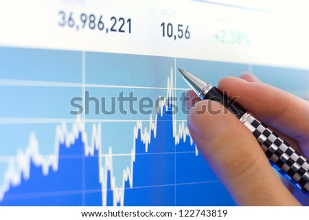 Business analyze with a pen, stock market graph close up on lcd screen - stock photo