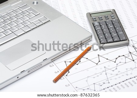 Business analyze with laptop, calculator and printed data sheet - stock photo