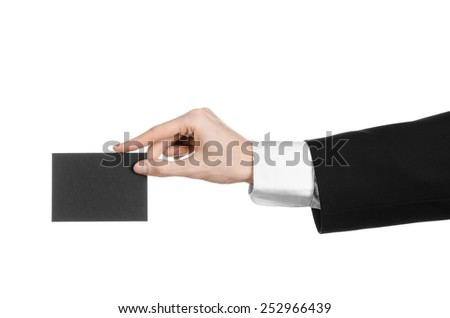 Business and advertising topic: Man in black suit holding a black blank card in hand isolated on white background in studio - stock photo