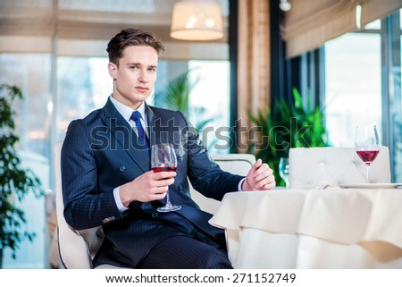 Business and alcohol. Confident businessman in formal wear sitting at a table in a restaurant while holding a glass of wine and looking ahead - stock photo