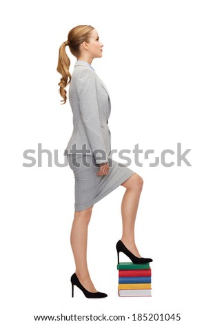 business and education concept - businesswoman stepping on pile of books - stock photo