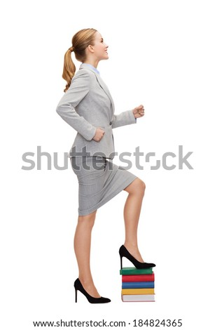 business and education concept - smiling businesswoman stepping on pile of books - stock photo