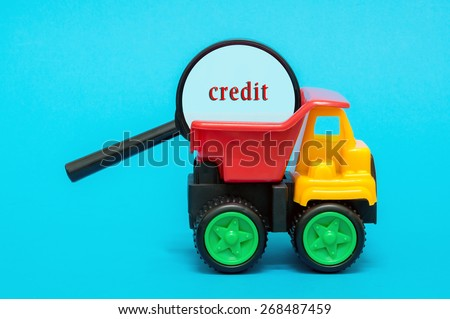 Business and finance concept. Toy lorry carrying a magnifying glass looking for word CREDIT on blue background - stock photo
