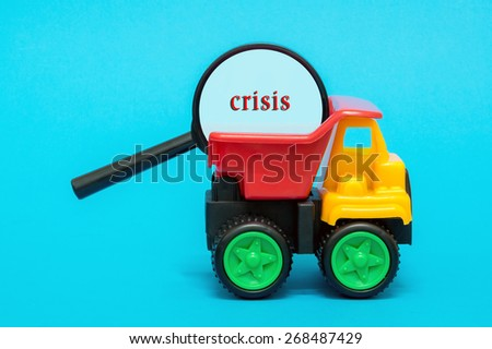 Business and finance concept. Toy lorry carrying a magnifying glass looking for word CRISIS on blue background - stock photo