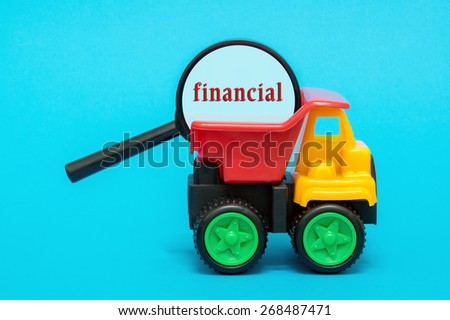 Business and finance concept. Toy lorry carrying a magnifying glass looking for word FINANCIAL on blue background - stock photo