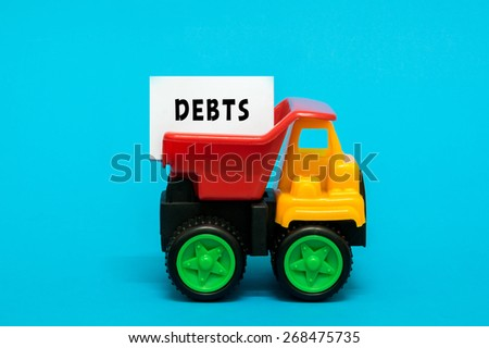Business and finance concept. Toy lorry transporting a DEBTS note on blue background. - stock photo
