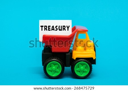 Business and finance concept. Toy lorry transporting a TREASURY note on blue background. - stock photo