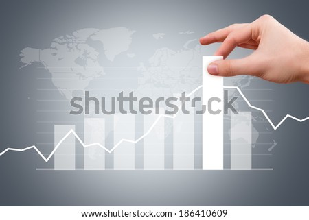 Business and finance concept, young male hand pulling bar of graph chart on digital screen with earth map background. - stock photo