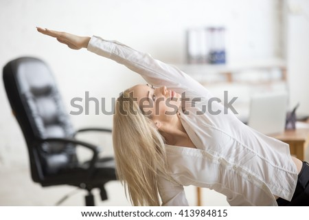 Business and healthy lifestyle concept. Portrait of young office woman doing fitness exercise at workplace. Happy beautiful business lady doing side bending posture on her break time - stock photo