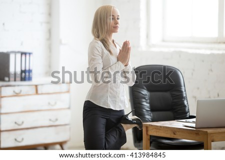 Business and healthy lifestyle concept. Portrait of young yogi office woman doing yoga at workplace. Calm beautiful business lady in formal wear and high heels standing in Tree posture, Vrksasana - stock photo