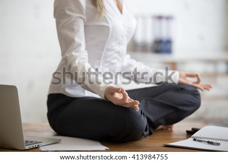 Business and healthy lifestyle concept. Young yogi office woman sitting cross-legged in half lotus yoga pose at workplace. Smart casual business lady meditating on her break time. Close-up - stock photo