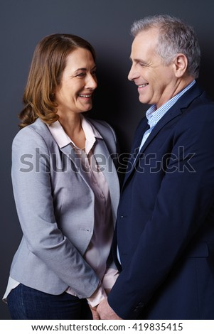 Business and life partners stand face to face and smile while resting against a dark blue background - stock photo