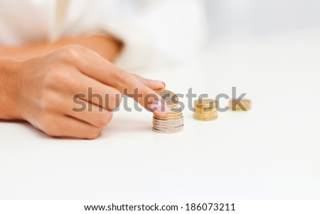 business and money saving concept - close up of female hand putting euro coins into columns in office - stock photo
