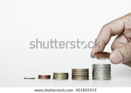 business and money saving concept, close up of male hand putting baht coins into columns
