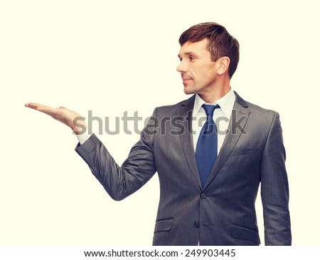 business and office concept - attractive buisnessman or teacher showing something on the palm - stock photo