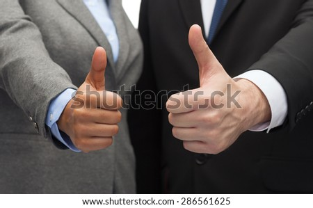 business and office concept - businessman and businesswoman showing thumbs up - stock photo