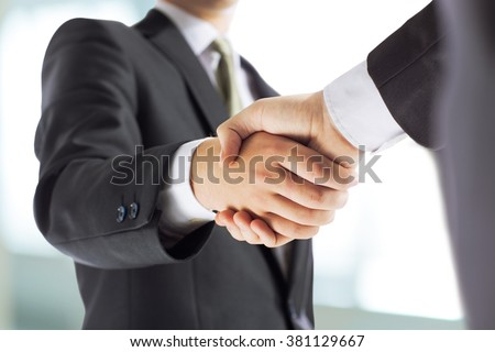 business and office concept - businessman shaking hands each oth