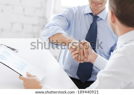 business and office concept - businessmen shaking hands in office - stock photo
