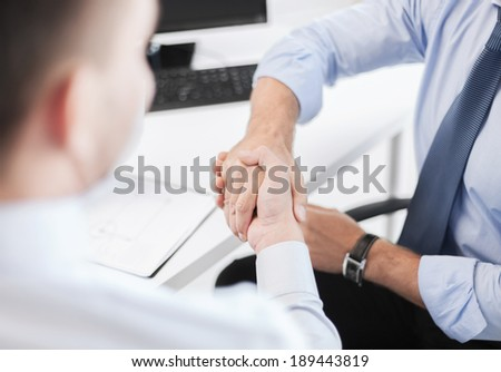 business and office concept - businessmen shaking hands in office
