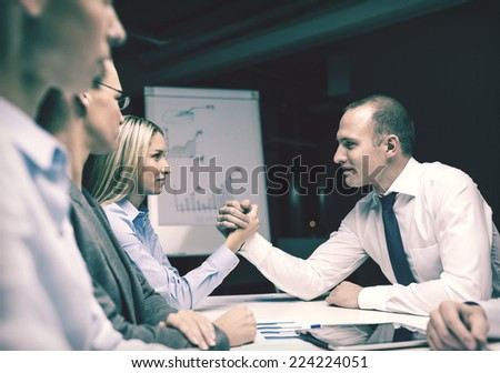 business and office concept - businesswoman and businessman arm wrestling during meeting in office - stock photo