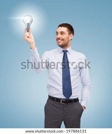 business and office concept - handsome businessman holding light bulb - stock photo