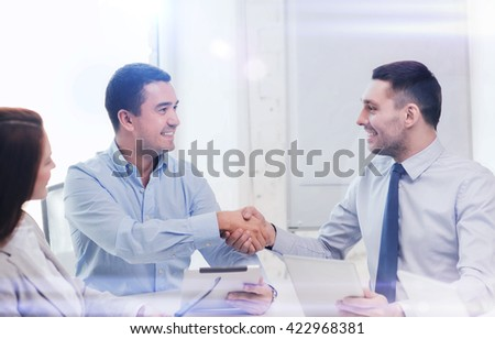business and office concept - smiling business team with tablet pc computers in office shaking hands