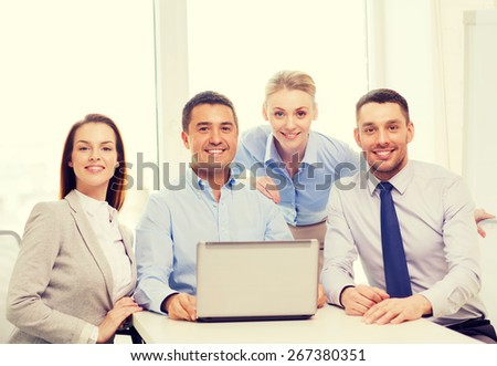 business and office concept - smiling business team working with laptop computer in office - stock photo