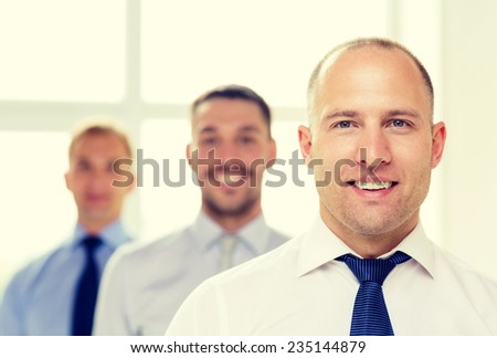 business and office concept - smiling businessman in office with team on the back - stock photo