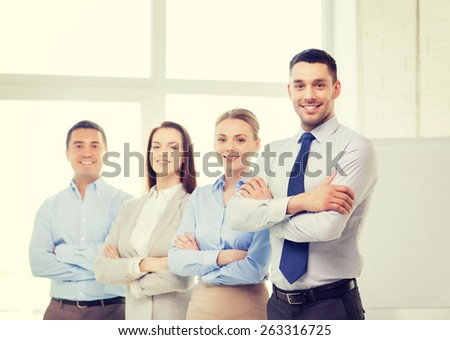 business and office concept - smiling handsome businessman with crossed hands and team in office - stock photo