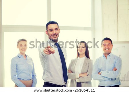business and office concept - smiling handsome businessman with team in office pointing finger at you - stock photo