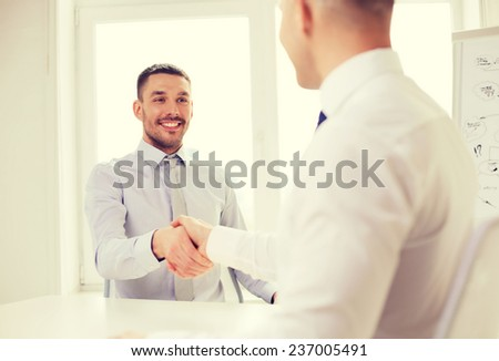 business and office concept - two smiling businessmen shaking hands in office - stock photo