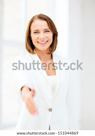 business and partnership concept - businesswoman with an open hand ready for handshake - stock photo