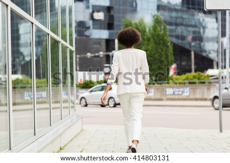 business and people concept - young african american businesswoman walking in city - stock photo