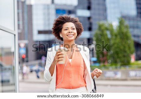business and people concept - young smiling african american businesswoman with coffee cup in city - stock photo